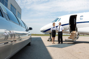 Flight attendant and pilot standing neat limousine and private jet at airport terminal